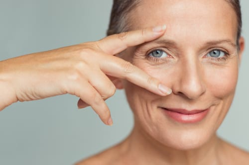 smiling senior woman with perfect skin showing victory sign near eye-img-blog