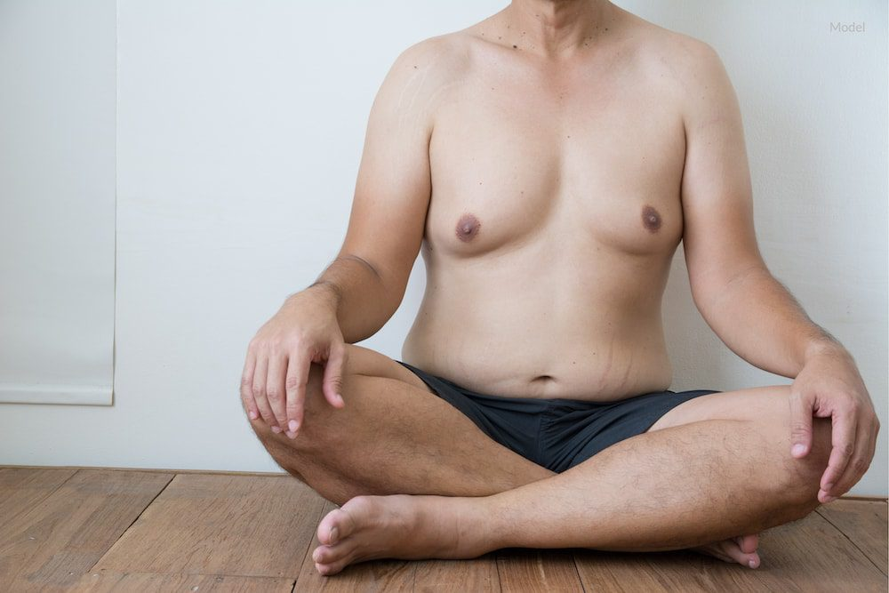 Man with gynecomastia sitting down.