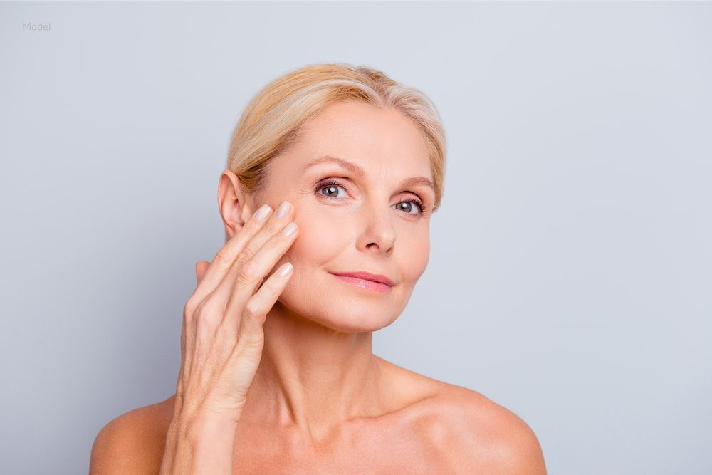 Middle aged woman touching and examining her face for signs of aging.