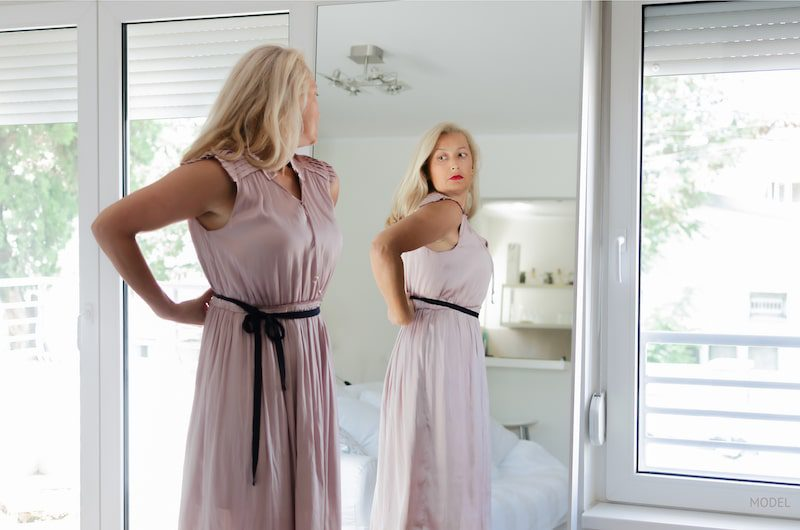 Woman looking at herself in the mirror while considering plastic surgery.